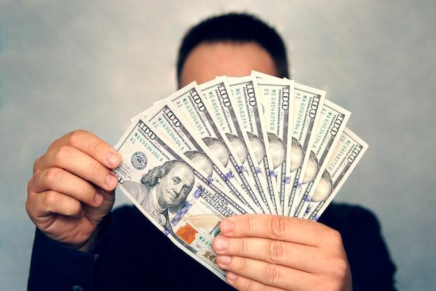 Kobieta liczy banknoty. ręce człowieka, które biorą pod uwagę dolary amerykańskie. w rękach dużo pieniędzy, nominałów 100 dolarów.
