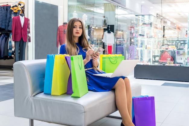 Kobieta liczy dolary na zakupy online z laptopem
