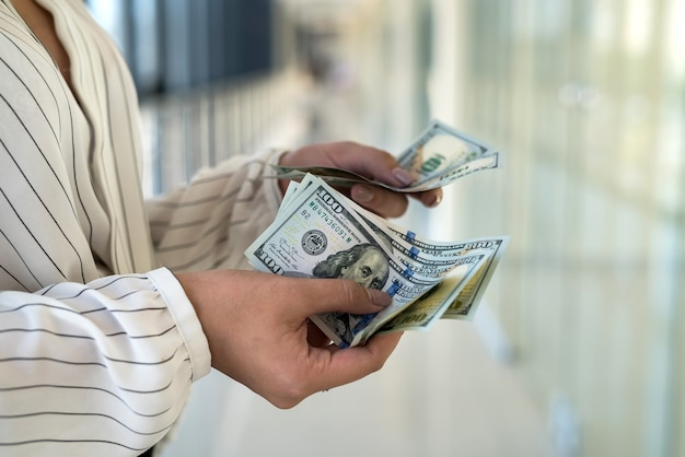 Kobieta liczy dolary w centrum handlowym po udanym zakupie