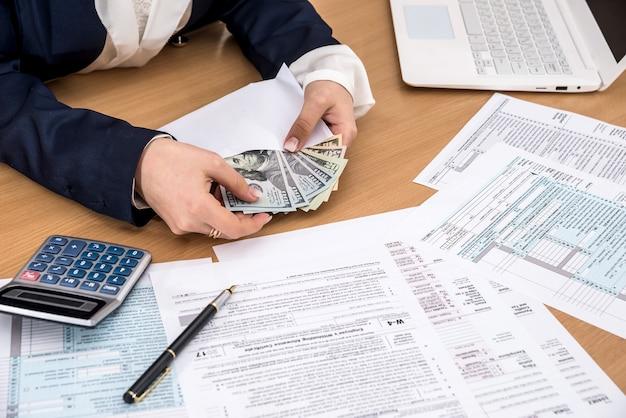 Kobieta liczy pieniądze wypełniając formularze podatkowe