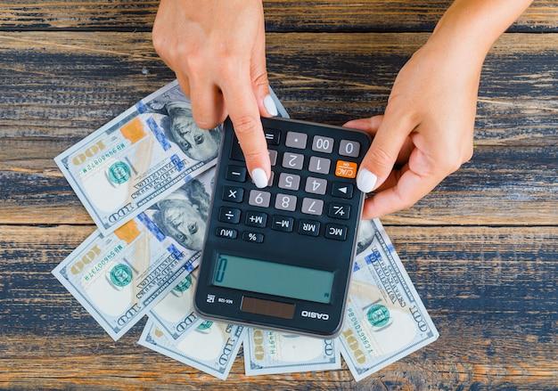 Kobieta liczy pieniądze za pomocą kalkulatora
