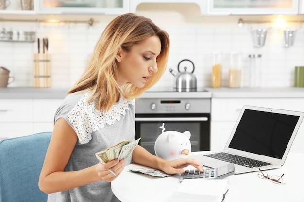 Kobieta liczy podatki przy stole w pomieszczeniu