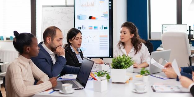 Kobieta, liderka firmy, rozmawiająca z różnorodną grupą