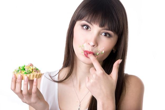 Kobieta lizanie jej palce podczas jedzenia ciasta