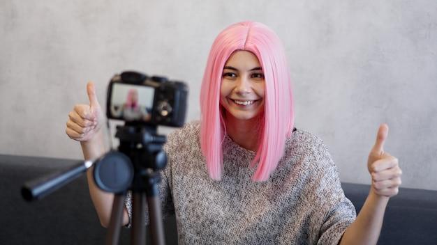 Kobieta lub blogerka z kamerą nagrywającą wideo i pokazującą kciuki w górę w domu
