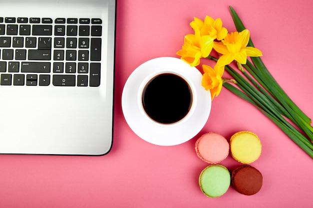 Kobieta lub kobiecy obszar roboczy z notatnikiem, kawą, makaronikami i kwiatami
