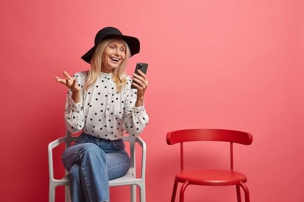 Kobieta lubi komunikować się online za pośrednictwem smartfona, ubrana w modny strój pozuje na krześle, rozmawia z daleka na różowo