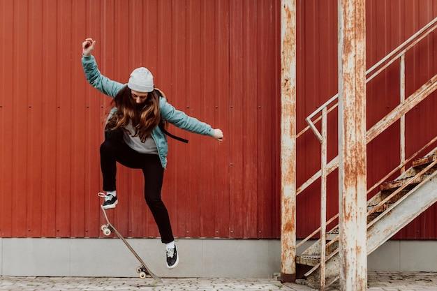 Kobieta łyżwiarz uprawia deskorolkę na świeżym powietrzu