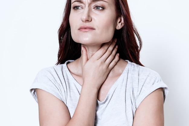 Kobieta ma ból gardła. grymas na jego twarzy.