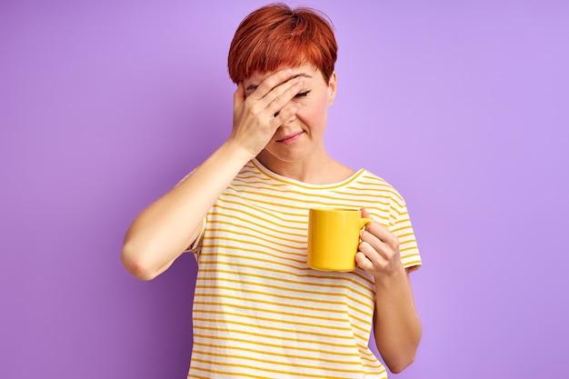 Kobieta ma ból głowy, trzyma kubek w dłoniach, źle się czuje. na białym tle na fioletowej ścianie