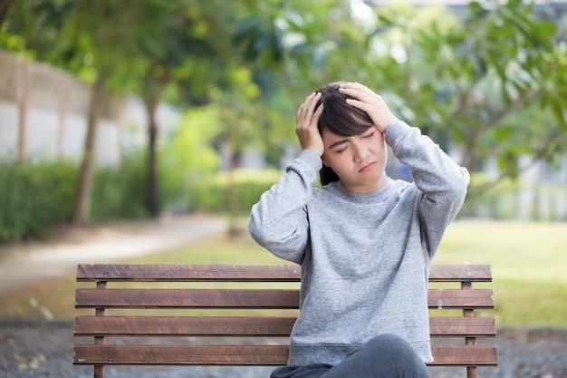 Kobieta ma ból głowy w parku