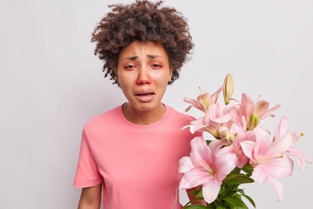 Kobieta ma czerwone opuchnięte oczy reaguje na alergen trzyma bukiet lilii nosi koszulkę pozuje w pomieszczeniu