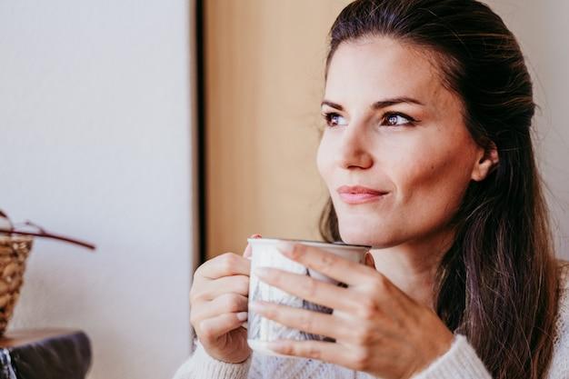Kobieta ma filiżankę herbaty w domu podczas śniadania.