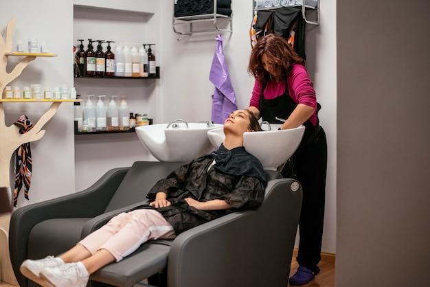 Kobieta ma jej włosy myjącego w salonie