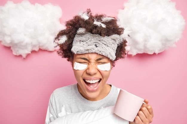 Kobieta ma kręcone włosy afro z przyklejonymi piórami głośno krzyczy lubi pić poranną kawę ubrana w piżamę poddana zabiegom kosmetycznym wyizolowana na różowo