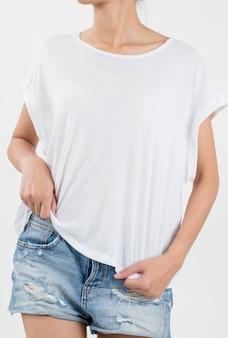 Kobieta ma na sobie białą koszulkę i krótkie jeansy na białym