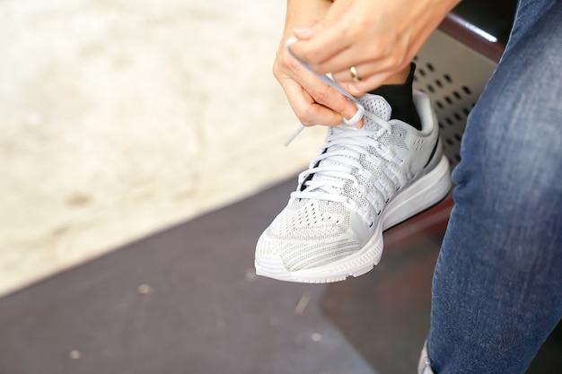 Kobieta ma na sobie białe tenisówki.