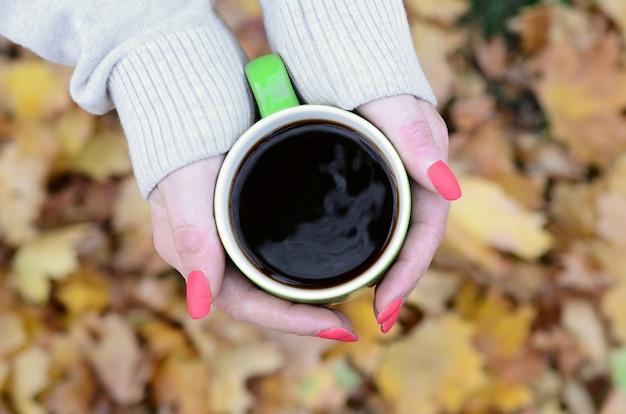 Kobieta ma na sobie biały sweter gospodarstwa filiżankę zielonej kawy