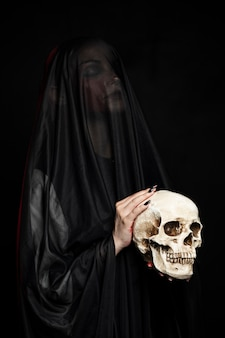 Kobieta ma na sobie czarny welon i trzyma czaszkę