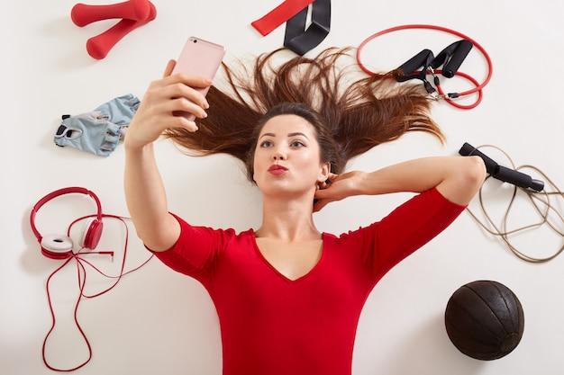 Kobieta ma na sobie czerwoną koszulę leżącą na białych powierzchniach otaczających różne urządzenia sportowe, ekspander, hantle, skopującą linę, gumki, kobieta bierze selfie i robi gest całowania.
