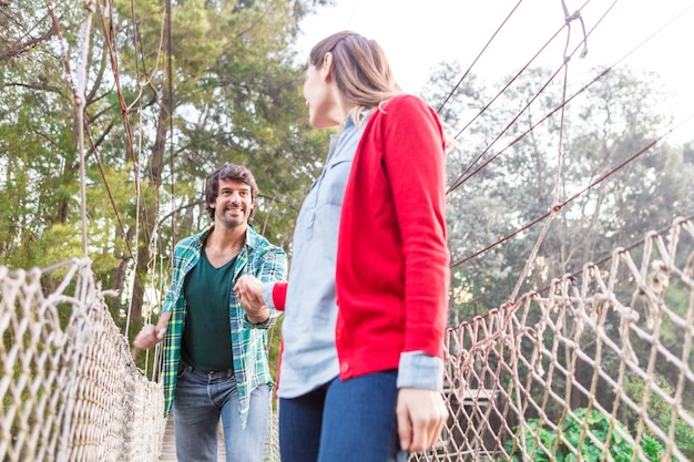 Kobieta ma na sobie czerwony sweter i trzymając za rękę swojego partnera