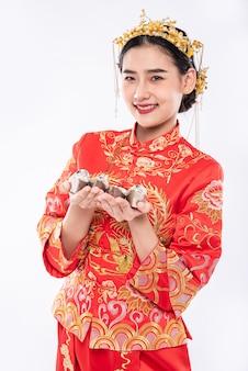Kobieta ma na sobie garnitur w stylu cheongsam i czarne buty gotowe do przekazania pieniędzy na prezent krewnemu
