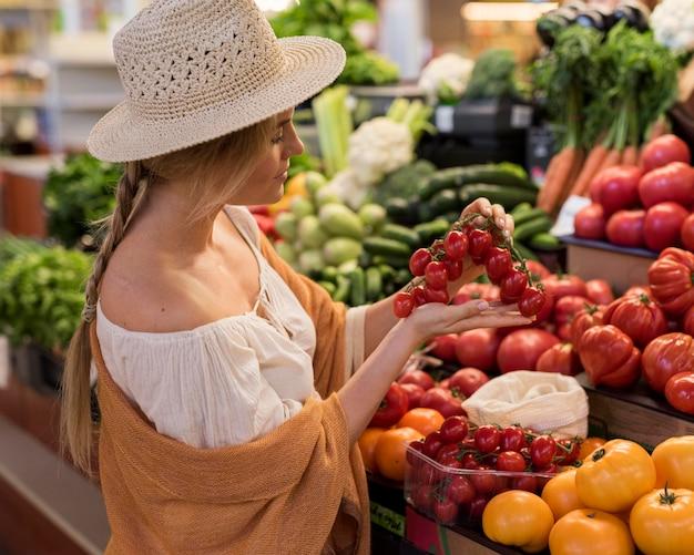 Kobieta ma na sobie kapelusz przeciwsłoneczny gospodarstwa pomidory czereśniowe