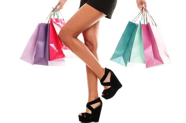 Kobieta ma na sobie kilka kolorowych toreb na zakupy