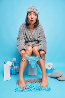 Kobieta ma na sobie maskę do spania szlafrok i koronkowe majtki ściągnięte na nogach sika na muszli klozetowej pozy w toalecie