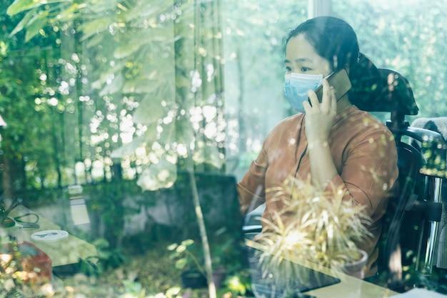 Kobieta ma na sobie maskę i dzwoni do ludzi, pracując na komputerze w domu. pandemia covid-19 (koronawirus).