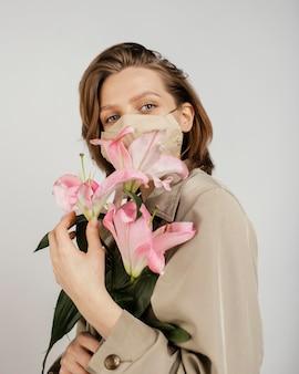 Kobieta ma na sobie maskę i trzyma bukiet kwiatów
