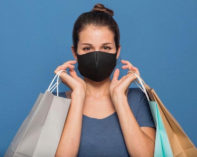 Kobieta ma na sobie maskę i trzyma torby na zakupy