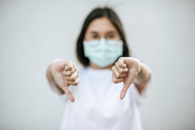 Kobieta ma na sobie maskę i wskazuje kciukiem w dół.