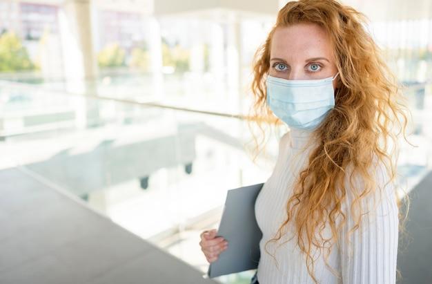 Kobieta ma na sobie maskę medyczną i trzyma dokument