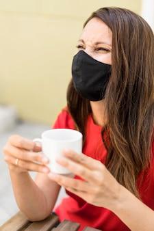 Kobieta ma na sobie maskę z tkaniny i trzyma filiżankę kawy