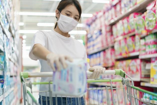 Kobieta ma na sobie maski chirurgiczne i rękawiczki, kupując podpaski w supermarkecie. panika po pandemii koronawirusa.