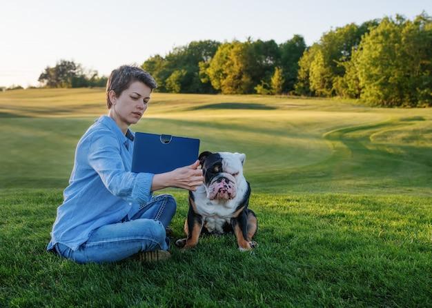 Kobieta ma na sobie niebieską koszulę, dżinsy pokazuje coś lub uczy czarno-białego psa na łące / zielonej trawie w słoneczny wiosenny ciepły dzień w parku