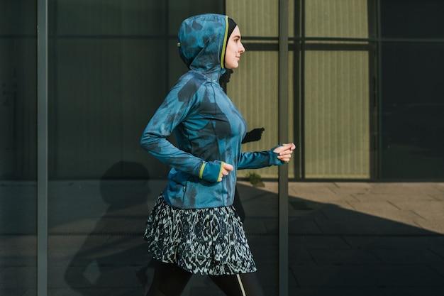 Kobieta ma na sobie niebieską kurtkę i szkolenia