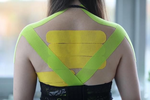 Kobieta ma na sobie taśmy kinesio na plecach i ramionach w gabinecie lekarskim