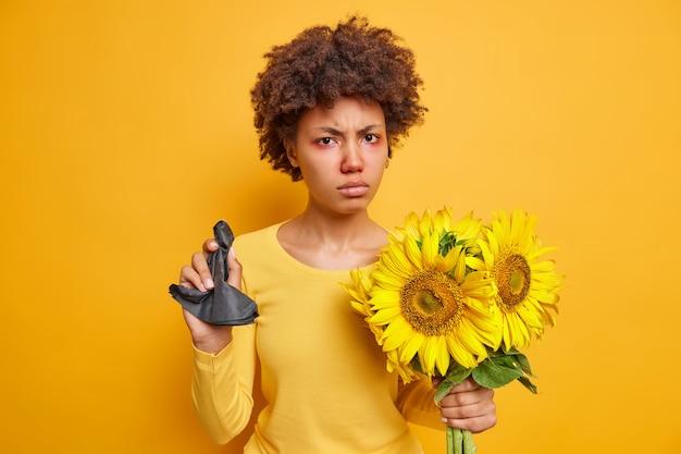 Kobieta ma nadąsany wyraz twarzy trzyma czarną papierową chusteczkę słoneczniki cierpi na alergię czerwone opuchnięte oczy odizolowane na żywym żółtym