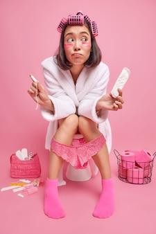 Kobieta ma niepewny wyraz twarzy wybiera między tamponem a podpaską menstruacyjną pozuje na toalecie ma na sobie biały szlafrok robi fryzurę nakładając łaty