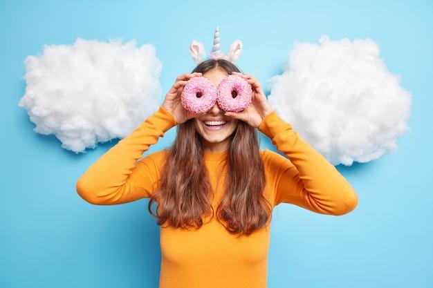 Kobieta ma oczy z dwoma pysznymi pączkami uśmiecha się szczęśliwie ma dobry nastrój nosi pomarańczowy sweter opaskę jednorożca lubi jeść smaczny deser
