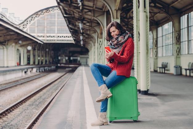 Kobieta ma pozytywny wygląd, siedzi ze skrzyżowanymi nogami przy torbie, trzyma telefon komórkowy