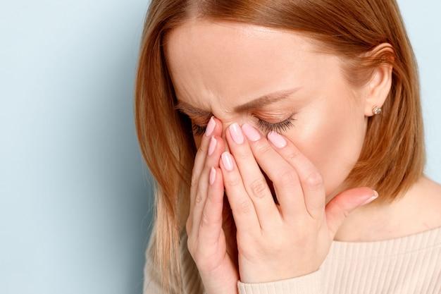 Kobieta ma problem z soczewkami kontaktowymi, ocierając opuchnięte oczy z powodu pyłków, alergii na kurz. zespół suchego oka