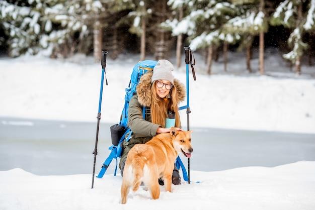 Kobieta ma przerwę podczas zimowych wędrówek, głaszcząc swojego psa w ośnieżonych górach w pobliżu jeziora i lasu