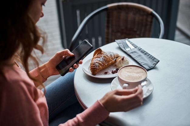 Kobieta ma śniadanie w caffe i przy użyciu smartfona. dziewczyna na czacie i za pomocą internetu z telefonem podczas przerwy na kawę z rogalikiem