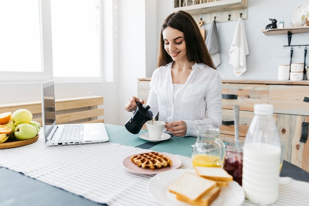 Kobieta ma śniadanie w kuchni
