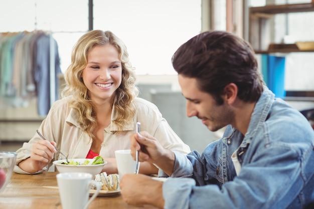 Kobieta ma śniadanie z kolegą w biurze