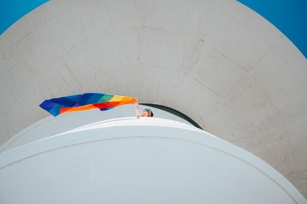 Kobieta macha flagą dumy gejowskiej ze szczytu budynku