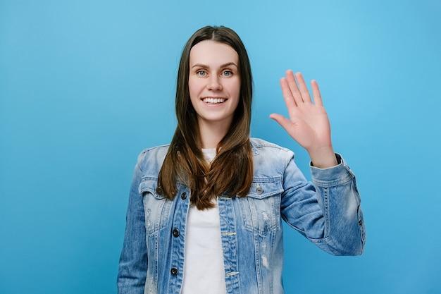Kobieta macha ręką, patrząc pozytywnie na kamerę